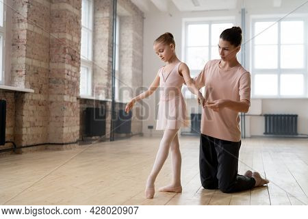 Little girl learning to dance ballet with the help of her trainer in dance studio