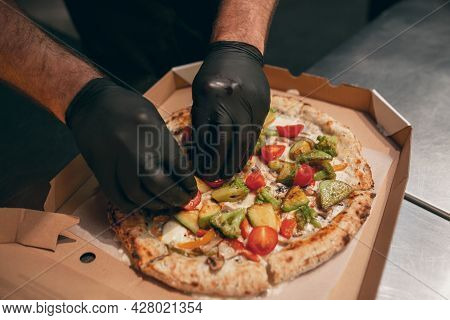 Close-up. Chef Putting Fried Vegetables Over Hot Tasty Pizza In A Cardboard Box. Looks Tasty, Delici