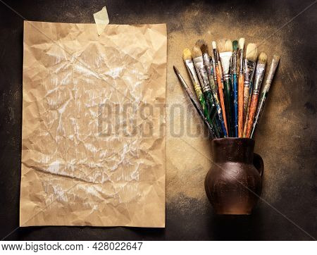 Paint brush in clay jug at  art painting canvas as abstract background texture. Paintbrush for painting and craft paper for artistic paint still life. Abstract art concept