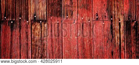 Old red barn in field late fall or autumn brown grass weathered wood
