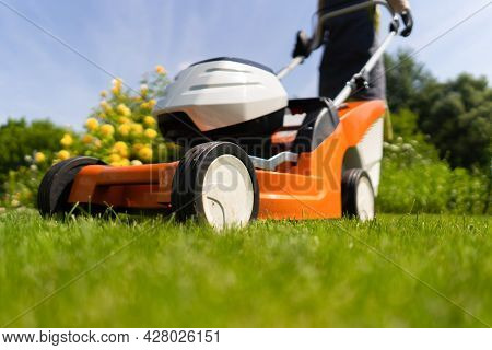 A Young Girl Is Mowing A Lawn In The Backyard With An Orange Lawn Mower. A Woman Gardener Is Trimmin