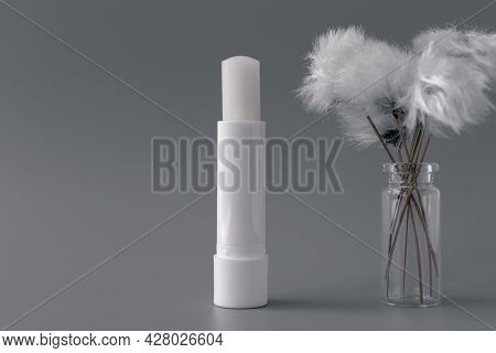 Side View Of Hygienic Lip Balm And Fluffy White Flower On Gray Background.