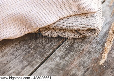 Autumn Or Winter Background. Stack Of Cozy Knitted Wool Clothes Sweaters And Dried Plant On Wooden T