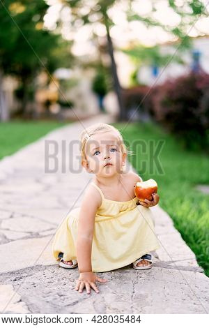 Little Girl With An Apple In Her Hand Squatted On A Paved Path