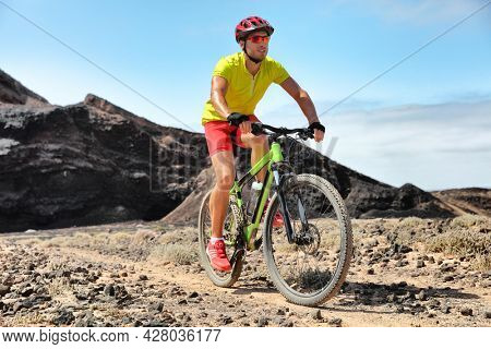 Biking MTB mountain bike on outdoor trail cycle track. Man cycling biker with helmet and accessories.