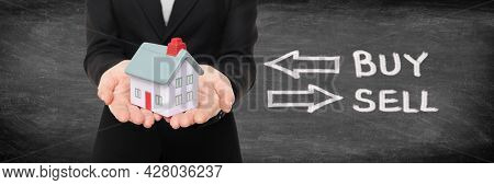 Real estate broker showing miniature house for buy and sell home housing market concept. Panoramic banner on black blackboard woman holding home with graphic design.