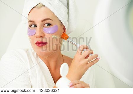 Woman Applies Makeup To Her Face, Selective Focus On Skin And Brush. Applying Foundation To Pigmente
