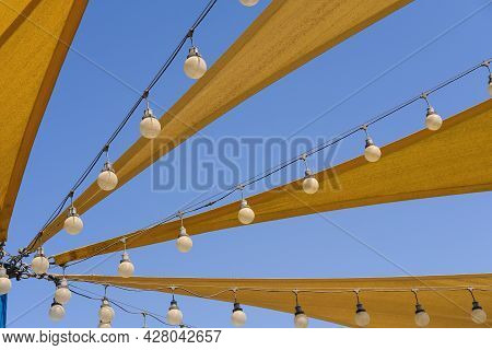 Dynamic Airy Texture Of Yellow Fabric Stretch Roof Made Of Canvas Sail With Rows Of Bulb Lamps For P