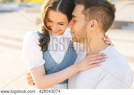 Close-up Portrait Of Young Loving Couple Resting In City Park Sitting Embracing On Bench In Summer S
