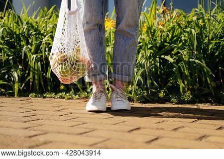 Woman In Jeans Standing And Holding White Mesh Bag With Fruits. Eco Friendly, Reusable Shopping Bag.