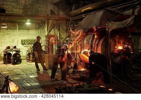 Steel workers melting iron in furnace steel mill