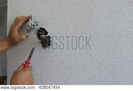 Hands Of An Electrician Working With The Replacement Of A Switch Against The Background Of An Empty