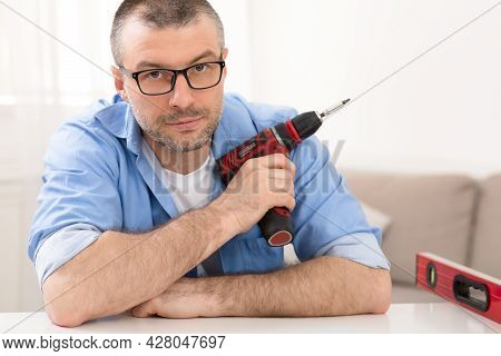 Portrait Of Mature Man Posing Holding Electric Drill At Home