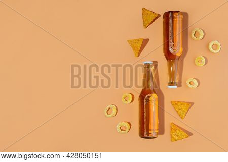 A Two Bottles Of Craft Lager And Porter Beer And Nachos Snack And Pistachios On Beige Background. In