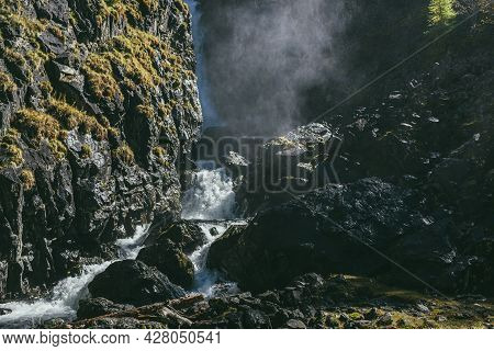 Mountain Autumn Landscape With Vertical Big Waterfall And Water Cloud Of Drops Above Turbulent River