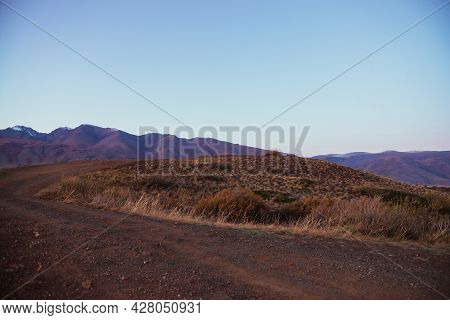 Scenic Autumn Landscape With Dirt Road On Mountain Pass With Orange Grasses And Shrubs With View To
