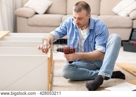 Mature Man Assembling Shelf Using Electric Drill Tool At Home