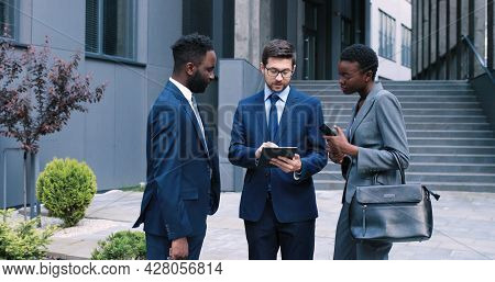 Serious Professional Male Advisor Consulting Clients Or Colleagues, Talking And Having Business Conv
