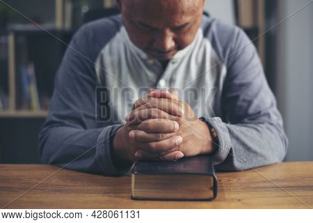 Prayer And Bible Concept. Asian Senior Man Praying, Hope For Peace The World And Free From Coronavir