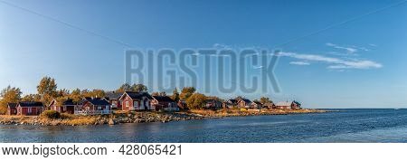 Idyllic Baltic Sea Panorama Landscape With Red Cottages On The Shoreline Under A Blue Sky In Autumn