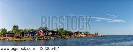 Idyllic Baltic Sea Panorama Landscape With Red Cottages On The Shoreline Under A Blue Sky