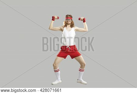 Funny Skinny Athlete Doing Fitness Exercise With Dumbbells Isolated On Gray Background