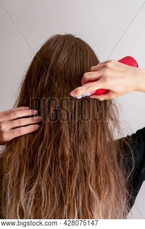 Young Woman Hand Holds Bottle And Spraying Her Wavy Blond Long Hair For Making It Silk And Soft. Hai
