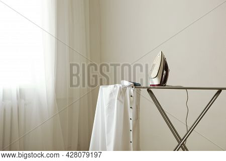 Iron And A Clothes On An Ironing Board On A Colored Background.