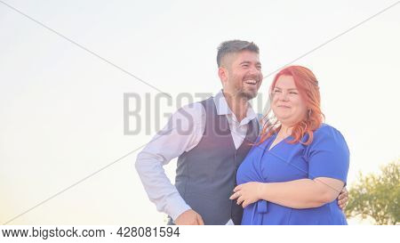 Turkish Man And His Beloved Caucasian Plus Size Red Headed Woman Embracing And Laughing. Mixed Race
