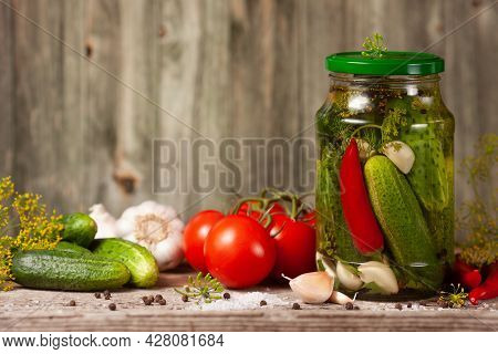 Pickled Cucumbers In Glass Jars And Spices And Vegetables For Preparation Of Pickles On Wooden Backg