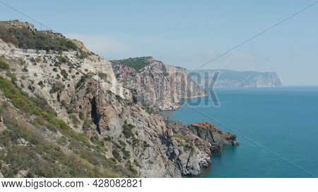 Picturesque Coast With Rocky Cliffs And Blue Sea. Action. Seascape With Rocky Coast. Amazing Beauty