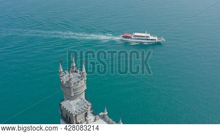 Castle On Background Of Yacht In Blue Sea. Action. Top View Of Beautiful White Castle Near Sea Cliff