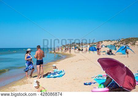Anapa, Russia-09.08.2020: Tourists Swim And Sunbathe On The Sandy Beach Of The Black Sea Coast. Trav