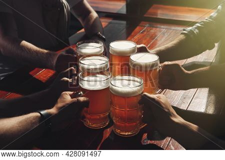 Friends Clinking Glasses With Beer At Table, Closeup