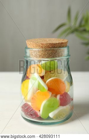 Delicious Fruity Gummy Candies In Glass Jar On White Wooden Table