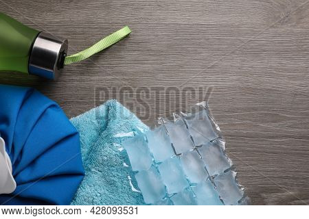 Bottle Of Water, Ice Pack, Cold Compress And Towel On Wooden Background, Flat Lay With Space For Tex
