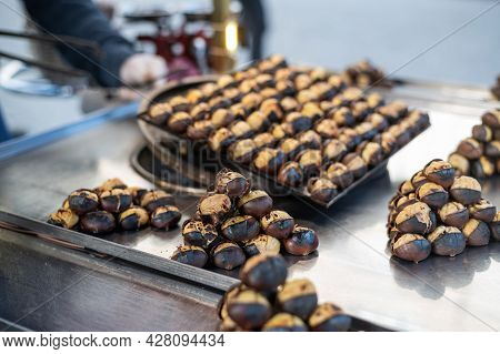 Male Salesman Is Cooking Roasted Chestnuts On A City Street. Street Food, Hot Cooked Chestnuts