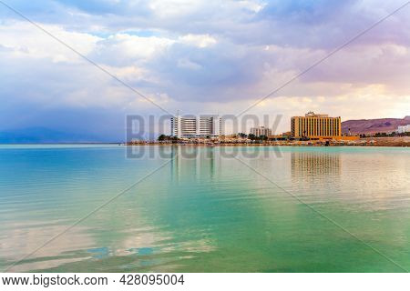 The smooth surface of the salty sea reflects the sky and clouds. Ancient terracotta-colored mountains. Low winter clouds are reflected in the green water. Israel, legendary Dead Sea