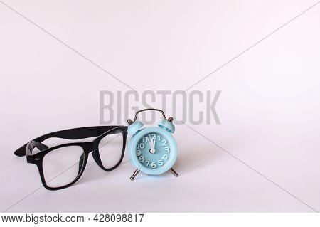 Black Glasses And A Blue Alarm Clock Shows 12 Twelve Oclock. Mock Up