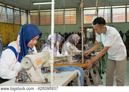 Male Tailor Supervisor Checks The Work Of The Tailors