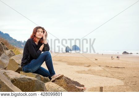 Biracial Teen Girl Sitting On Rocky Shore Near The Ocean In The Pacific Northwest On Foggy Day