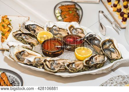 Fresh Oysters Close-up. Served Table, Lemon And Ice. Healthy Seafood. Fresh Oyster Dinner In Restaur