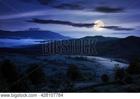 Mountainous Countryside Landscape At Night. Trees And Agricultural Fields On Hills Rolling In To The