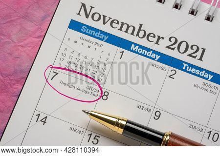 November 2021, spiral desktop calendar with the end of daylight saving time marked in red, business and time concept