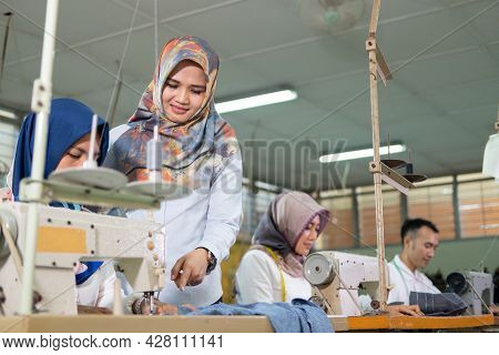 Female Supervisor In A Veil With A Pointing Finger Is Standing At The Side And Sees The Seamstress U