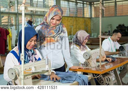 Emale Supervisor Stands To The Side And Sees The Seamstress Using The Sewing Machine