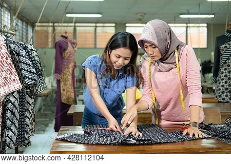 Seamstresses And Supervisors Measure The Fabric With A Ruler Before Sewing It