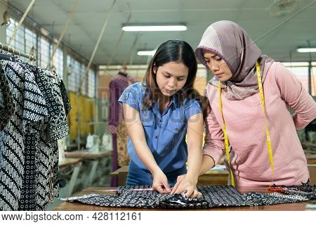 Asian Seamstresses And Work Supervisors Measure Fabrics With A Ruler According To The Rules
