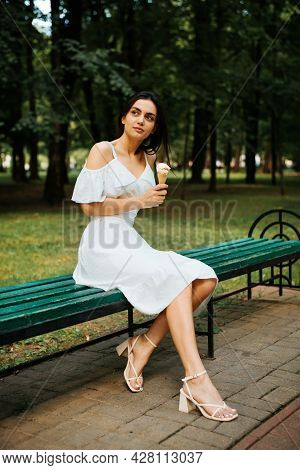Beautiful Young Brunette Woman In A White Summer Dress Holding Ice Cream And Relaxing On A Park Benc