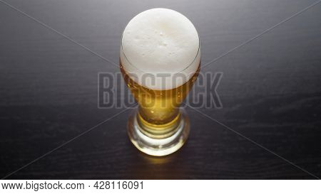 Beer in glass, view from above. Half pint of frothy fresh lager beer on table. Top view.